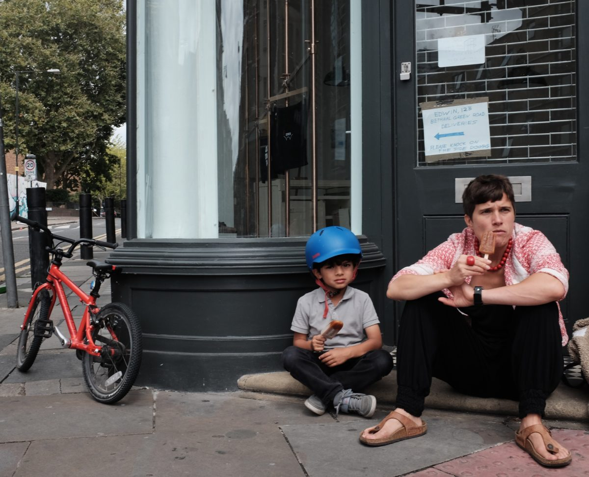 Woman and child on shop front step eating ice cream in shoreditch