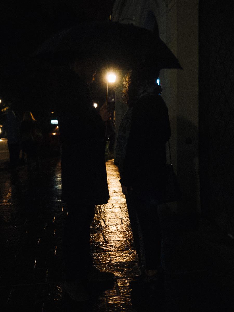 Couple in the rain at night under umbrella in krakow